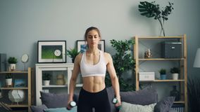 Mujer joven fuerte en la ropa de deportes que hace ejercicios con pesas de gimnasia en el apartamento almacen de metraje de vídeo
