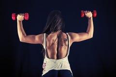 Mujer joven fuerte que hace la prensa del empuje de la pesa de gimnasia Fotografía de archivo