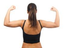 Mujer joven fuerte que muestra sus músculos Imagen de archivo libre de regalías