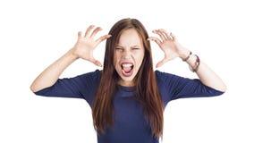 Mujer joven furiosa enojada con las manos aumentadas que se colocan y que gritan sobre el fondo blanco imagen de archivo libre de regalías