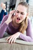 Mujer joven furiosa que grita en su smartphone, gente real Imagen de archivo libre de regalías