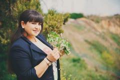Mujer joven gorda hermosa sonriente feliz en chaqueta azul marino al aire libre con las flores Mujer joven gorda confiada Mujer d Foto de archivo
