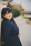 Mujer joven gorda hermosa sonriente feliz en chaqueta azul marino al aire libre en la calle Mujer joven gorda confiada Mujer de X Fotos de archivo