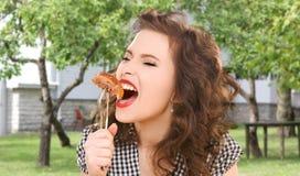 Mujer joven hambrienta que come la carne en la bifurcación sobre casa fotografía de archivo libre de regalías