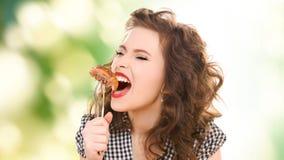 Mujer joven hambrienta que come la carne en la bifurcación sobre verde fotografía de archivo