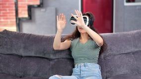 Mujer joven hermosa activa que goza llevando el simulador del casco de la realidad virtual en casa almacen de video