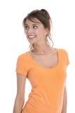 Mujer joven hermosa aislada en la camisa del albaricoque que mira de lado Imágenes de archivo libres de regalías