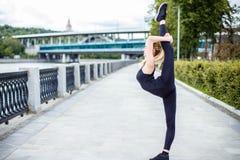 Mujer joven hermosa al aire libre que estira y que se prepara para la yoga y el ejercicio Imagenes de archivo