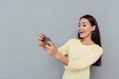 Mujer joven hermosa alegre que juega a los videojuegos en el teléfono móvil Fotos de archivo