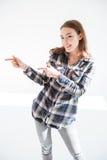 Mujer joven hermosa alegre que se coloca y que señala lejos Imagen de archivo