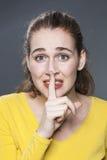 Mujer joven hermosa aterrorizada que quiere mantener cosas confidenciales Foto de archivo libre de regalías