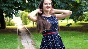 Mujer joven, hermosa, atractiva en un vestido elegante, presentando en cámara Ella ríe, presenta para la cámara, su pelo metrajes