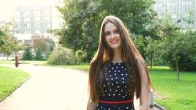 Mujer joven, hermosa, atractiva en un vestido elegante, presentando en cámara Ella ríe, presenta para la cámara, su pelo almacen de video