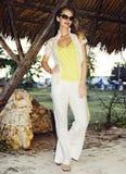 Mujer joven hermosa bajo una azotea de la palma foto de archivo