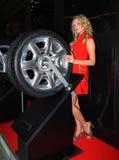 Mujer joven hermosa cerca de una rueda del coche. Foto de archivo