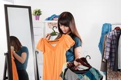 Mujer joven hermosa cerca del estante con ropa foto de archivo