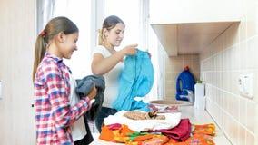 Mujer joven hermosa con el adolescente que clasifica la ropa sucia en lavadero Imágenes de archivo libres de regalías