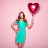 Mujer joven hermosa con el balón de aire de la forma del corazón fotografía de archivo