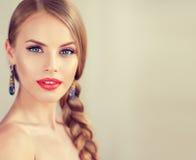 Mujer joven hermosa con el braidpigtail y pendientes grandes en ella fotos de archivo