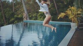 Mujer joven hermosa con el cuerpo atractivo en el traje de baño que salta adentro a una piscina almacen de metraje de vídeo