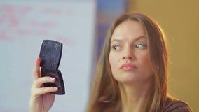 Mujer joven hermosa con el espejo que comprueba maquillaje del aspecto almacen de metraje de vídeo