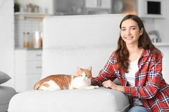 Mujer joven hermosa con el gato lindo en butaca Fotografía de archivo libre de regalías