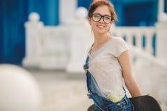 Mujer joven hermosa con el monopatín en ciudad Fotografía de archivo