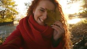 Mujer joven hermosa con el ojo cerrado largo del pelo rizado con la hoja del otoño Muchacha que sonríe en la cámara y la presenta metrajes