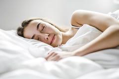Mujer joven hermosa con el pelo largo que duerme en cama en dormitorio Fotografía de archivo