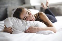 Mujer joven hermosa con el pelo largo que duerme en cama en dormitorio Fotos de archivo