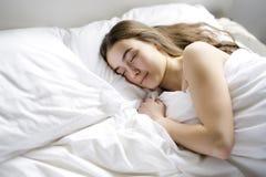 Mujer joven hermosa con el pelo largo que duerme en cama en dormitorio Imágenes de archivo libres de regalías