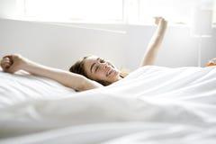 Mujer joven hermosa con el pelo largo que duerme en cama en dormitorio Imagen de archivo libre de regalías