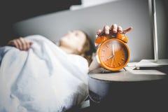 Mujer joven hermosa con el pelo largo que duerme en cama en dormitorio Fotografía de archivo libre de regalías