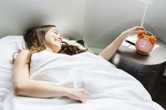 Mujer joven hermosa con el pelo largo que duerme en cama en dormitorio Fotos de archivo libres de regalías