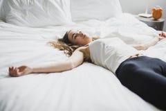 Mujer joven hermosa con el pelo largo que duerme en cama en dormitorio Foto de archivo