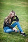 Mujer joven hermosa con el pelo largo que se sienta en la hierba verde Foto de archivo