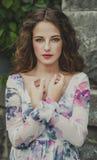 Mujer joven hermosa con el pelo marrón, labios rojos que se colocan en ston fotografía de archivo libre de regalías