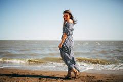 Mujer joven hermosa con el pelo negro en un vestido largo que se divierte en la playa del mar de Azov Foto de archivo