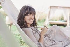 Mujer joven hermosa con el pelo oscuro en una hamaca, portr al aire libre Fotografía de archivo libre de regalías