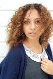 Mujer joven hermosa con el pelo que sopla del viento a través de la cara Imagen de archivo
