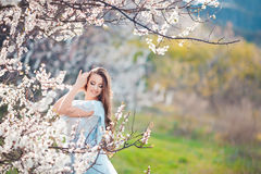 Mujer joven hermosa con el pelo que sopla sano largo que se relaja en parque en la puesta del sol Foto de archivo libre de regalías