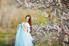 Mujer joven hermosa con el pelo que sopla sano largo que se relaja en parque en la puesta del sol Foto de archivo