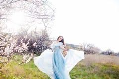 Mujer joven hermosa con el pelo que sopla sano largo que se relaja en parque en la puesta del sol Imágenes de archivo libres de regalías