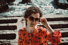 Mujer joven hermosa con el pelo rizado corto que mira la cámara Gafas de sol retras femeninas de la protecci?n del sol Disfrute d fotografía de archivo