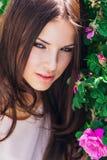 Mujer joven hermosa con el pelo rizado largo que presenta cerca de rosas en un jardín El concepto de publicidad del perfume Imagen de archivo libre de regalías