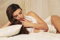 Mujer joven hermosa con el pelo rizado oscuro en la ropa interior elegante del cordón, presentando en dormitorio Fotos de archivo libres de regalías