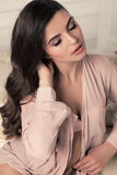 Mujer joven hermosa con el pelo rizado oscuro en la ropa interior elegante del cordón, presentando en dormitorio Foto de archivo libre de regalías