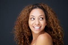 Mujer joven hermosa con el pelo rizado que ríe y que mira lejos Fotos de archivo libres de regalías