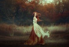 Mujer joven hermosa con el pelo rojo muy largo en un vestido medieval de oro que camina con el rojo del bosque del otoño de largo