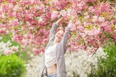 Mujer joven hermosa con el pelo rojo que se divierte que se coloca en árbol de la flor de cerezo Foto de archivo